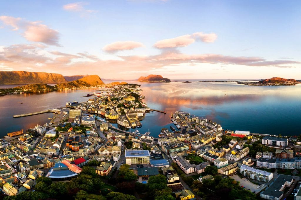 Alesund, Norway. Aerial view of Alesund, Norway at sunrise. Colorful sky over famous tourisitc destination with sunlight and mountains